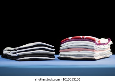 stack or pile of folded clothes, t-shirt of multiple colors perfectly ironed and folded on top of professional iron board with black background, selective focus, laundry, retail or textile business