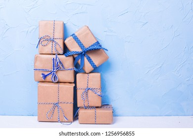 Stack or pile of wrapped boxes with presents on white textured background against blue wall. Selective focus. Place for text. Holiday shopping concept.