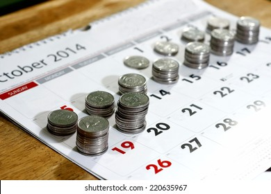 stack or piles of philippine peso coins and a calendar