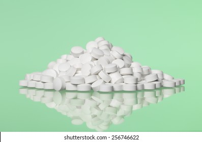 Stack of pills towards green background