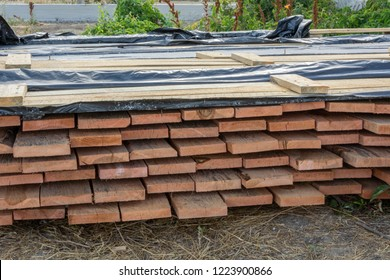 A stack of pine boards soaked in an antiseptic solution is dried at the construction site. Building materials for the construction of a frame house.