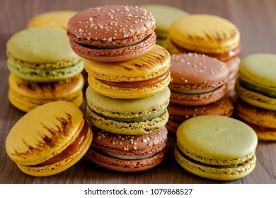 Stack of pistachio, almond and salted caramel macarons on brown wooden table in natural light