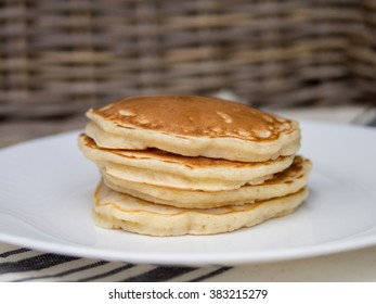 stack of plain fluffy pancakes on a white plate