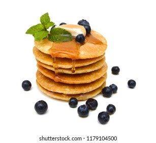 A stack of plain pancakes, syrup and blueberries on a white background.