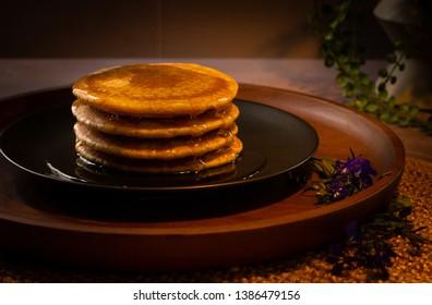 Stack of plain spelt wheat pancakes on wooden plate
