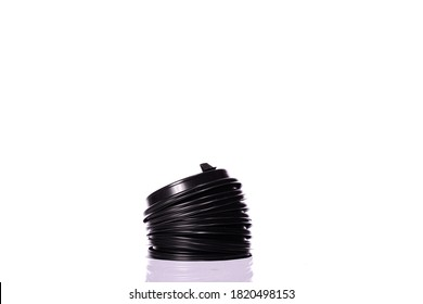 Stack of plastic disposable black top coffee caps for paper cups isolated on white background. Coffee to go, takeaway hot drinks, lids, ecology, recycling concept, environmental protection. Copy space