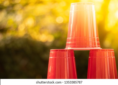 A stack of Plastic red solo drinking cups for beer pong or drinking games with green background on a white table.
