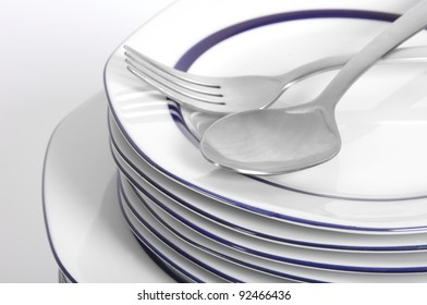 A stack of plate, knife and fork