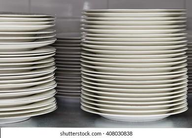 Stack of plates on the showcase. Restaurant utensils. Shallow focus