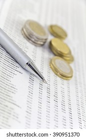 Stack of pound coins on financial figures balance sheet. Business background, financial data concept with numbers and money. Finance background with dollars and euro cents. Finance concept.