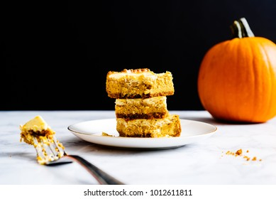 Stack of pumpkin cheesecake bars on a white plate with a dark navy blue background.