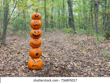 Stack of pumpkins with different facial expressions in the woods