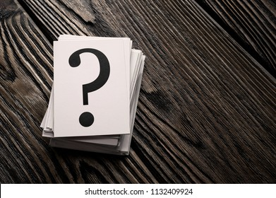 Stack of question mark cards on the wooden table with copy space