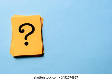 Stack of question marks on yellow cards arranged to the side on blue background with copy space