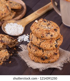 Stack of raisin pecan oatmeal cookies with a spoonful of oatmeal flakes in background