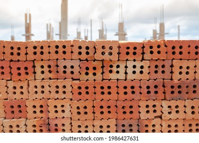 Stack of red bricks with construction site in background