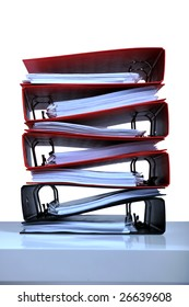 Stack of red folders on desk, white background