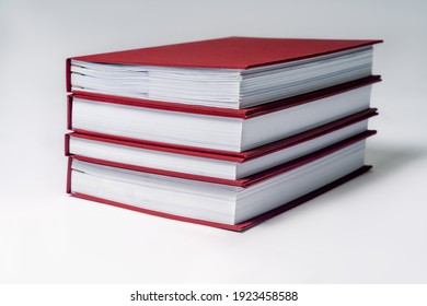 Stack of red hardcover books or reports on white background. Copy space.