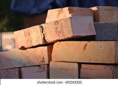 A stack of red refractory bricks at sunset