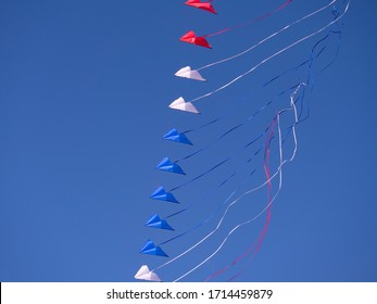 Stack of red, white an blue dual line stunt kites on a blue sky background.