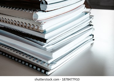 Stack of report papers lies on a desk ready for review