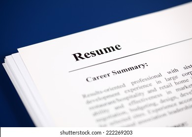 Stack of resumes on a blue background.