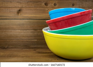 stack of retro colorful mixing bowls on rustic wood