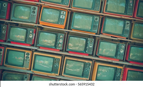 A stack of retro grunge portable televisions in vintage style.