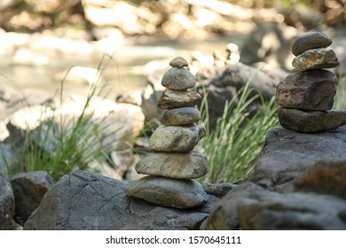 Stack of rocks along creek with cool tranquil water in background