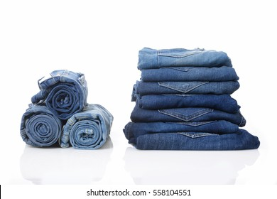 Stack of with roll blue jeans pants isolated on white with natural shadows