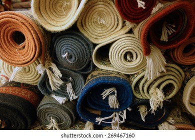 A stack of rolled-up mats or carpets in a variety of colors viewed end-on, in a carpet store in India. Textiles of all types are a major Indian export and a traditional  Indian manufacturing sector.