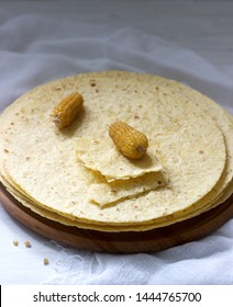 A stack of round corn tortillas on a wooden board and corncobs.