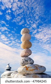 A stack of the round pebbles against the cloudy sky