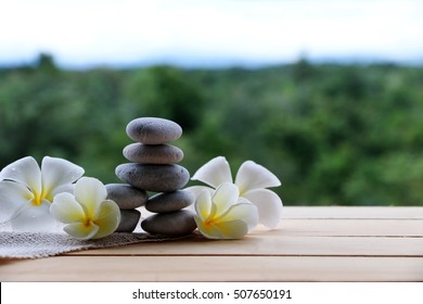 Stack of round smooth stones and frangipani white on the table natural backdrop.Spa concept