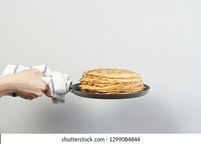 Stack of russian pancake blini in pan woman holds in hands on a grey background. Close-up with copy space