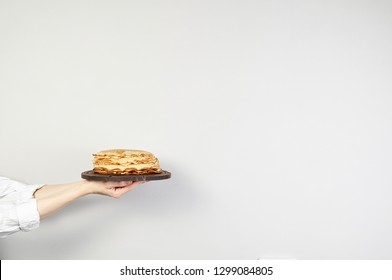 Stack of russian pancake blini in rustic wooden dish woman holds in hands on a grey background. Close-up with copy space