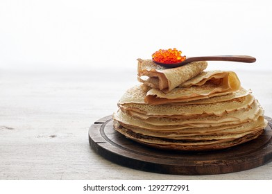 Stack of russian thin pancakes blini with red caviar. Shrovetide Maslenitsa festival meal on white background. Close up top view with copy space