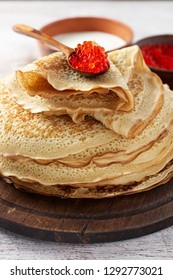 Stack of russian thin pancakes blini with red caviar and fresh sour cream. Shrovetide Maslenitsa festival meal on white wooden background. Rustic style, close up view