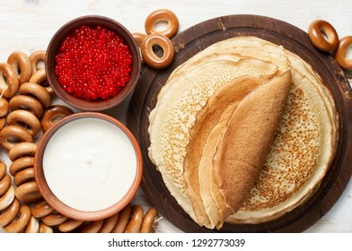 Stack of russian thin pancakes blini with red caviar and fresh sour cream. Shrovetide Maslenitsa Butter Week festival meal. Rustic style, close up top view