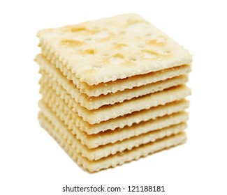 Stack of saltine crackers isolated on white.