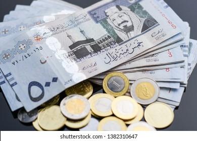 Stack of Saudi Arabia currency, Saudi Riyal paper of five hundreds riyals and Saudi Riyal coins on soft background.