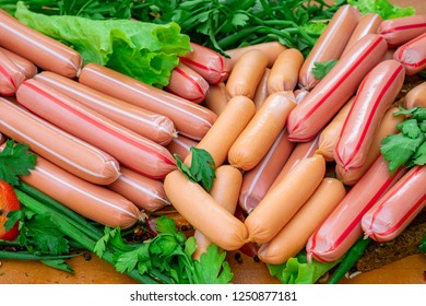 Stack of sausages with greens on wooden board closeup