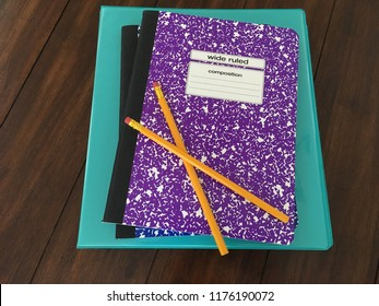 Stack of school supplies with pencils, notebook binder, and composition books on wooden table