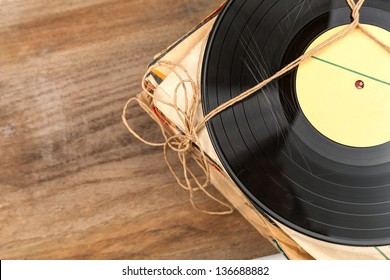 Stack of scratched dusty old vinyl records tied with rope on wooden table