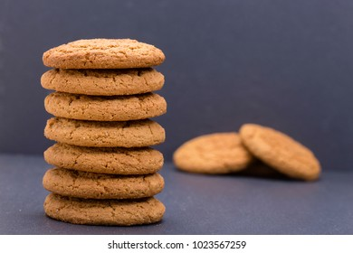 A stack of seven home made cookies - oat cookies on the background of black slate , close up