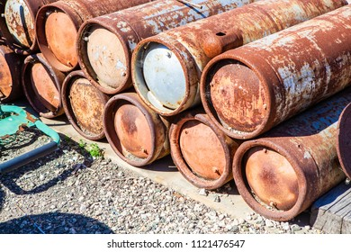 Stack of several decayed, rusty compressed gas cylinders in a yard