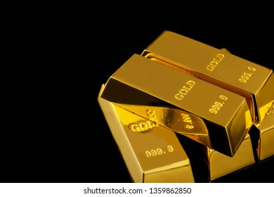 Stack of shiny gold bars on black background. Space for text