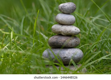 Stack of six pebbles in the lush, green grass, created by a child to learn about mindfulness.
