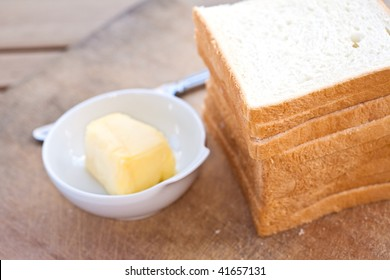 Stack of sliced bread with butter on an outdoor setting.