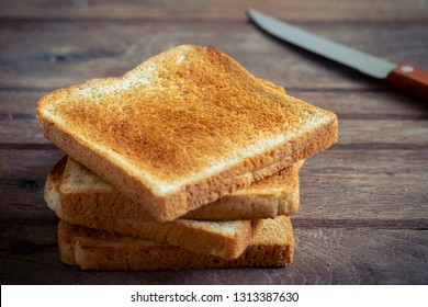 Stack of sliced toast on old wooden table